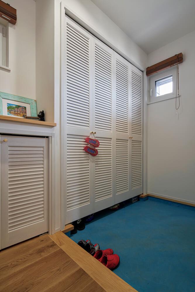 白を基調とした玄関には、外観に合わせて床にブルーのモールテックスを施工した