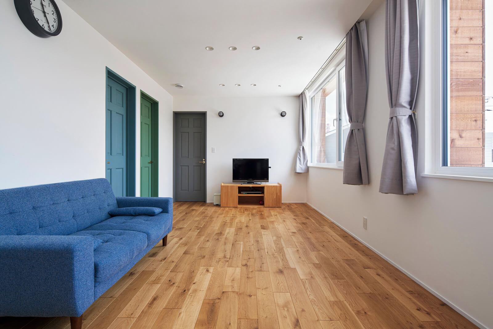 13帖の広さを備える2階フリースペース。各個室の木製ドアにはそれぞれが好きな色をペイントした