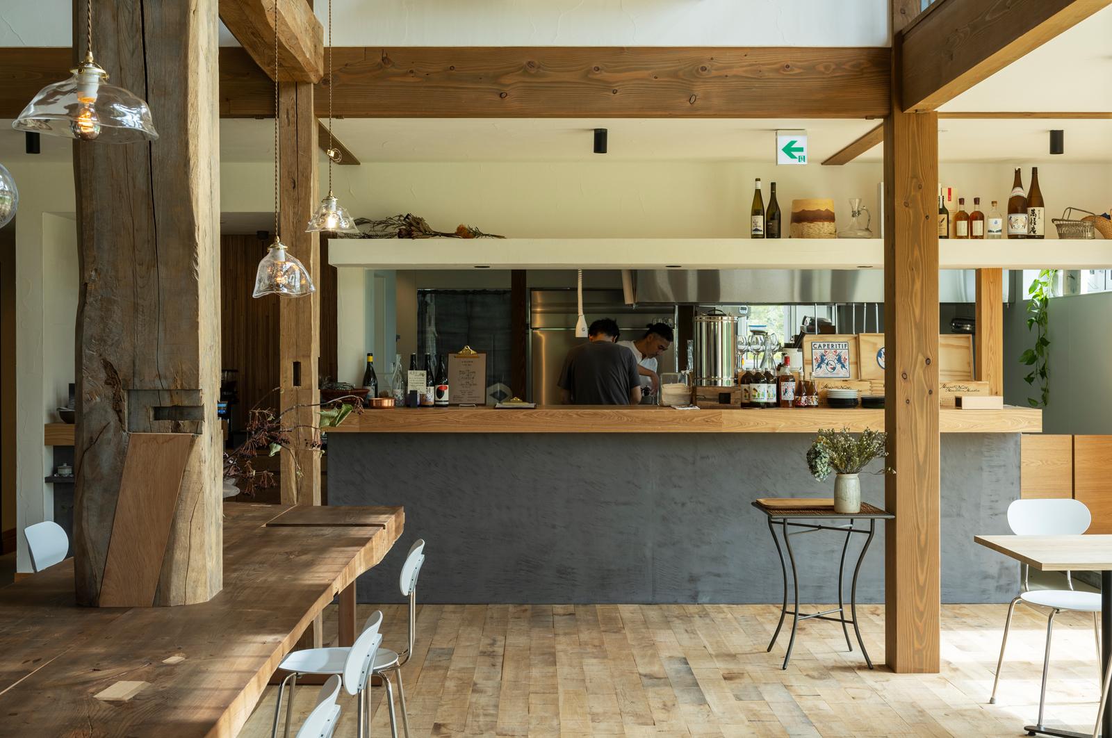 オープンキッチンのカウンターの墨色の腰壁は、工場仕上げのモールテックス。天板にはタモ無垢板を用いた