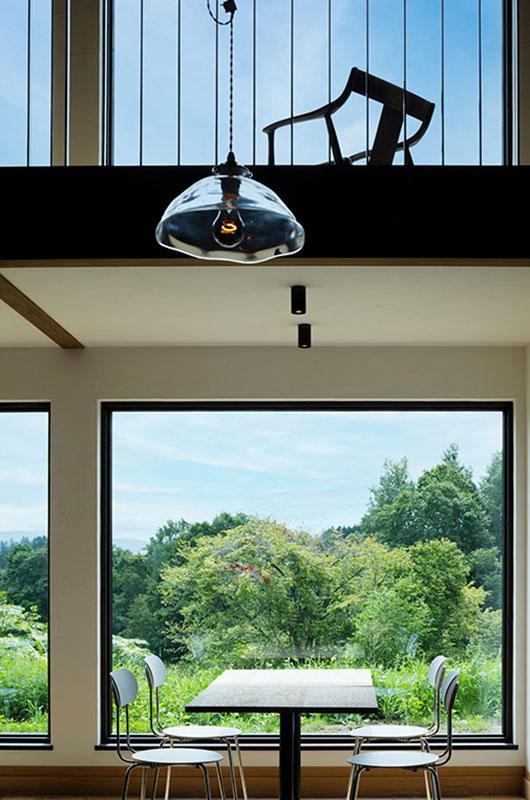 借景の緑が染み込む窓辺に置かれたテーブルは、ニレ無垢材を浮造りにした天板を採用。製作は、札幌の家具工房「621」
