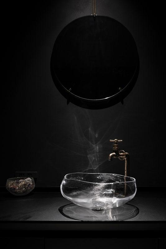 1階女性用トイレにも、洞爺湖をイメージしたという高臣さん制作の手洗いボウルを設置。照明に浮かび上がるガラスの揺らぎが、墨黒のシックな空間に映える