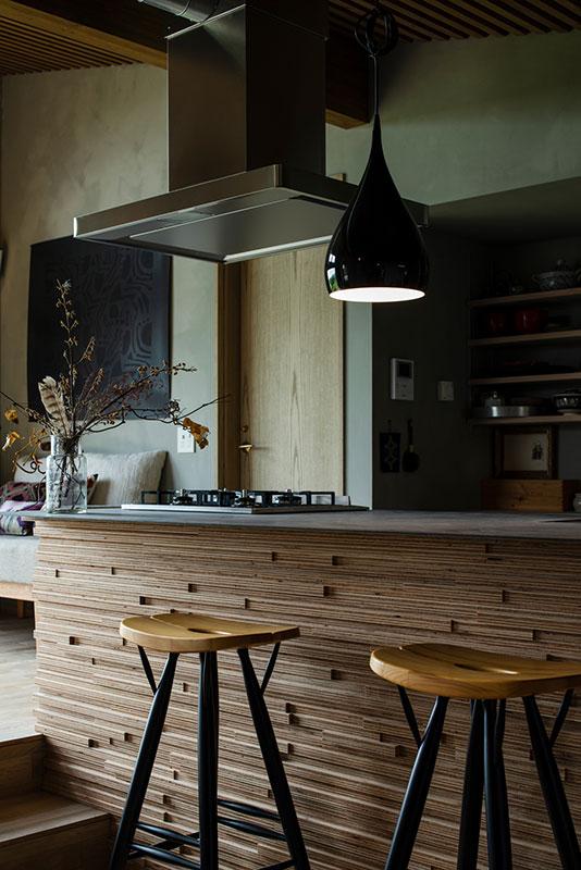 カラマツ合板を張り、リン酸処理のアイアンを天板にしたバーのようなキッチンは、三共建具工業の造作。大工造作の背面収納には、マカバ材の天板を採用