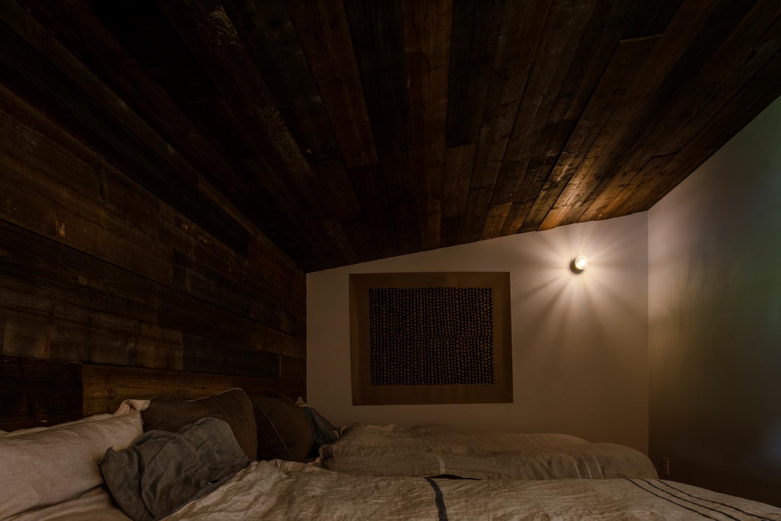 フランスの屋根裏部屋をイメージし、アンティーク加工を施した松材を天井に張った寝室。光沢が美しい壁は、大理石を混ぜたペンキで仕上げてある