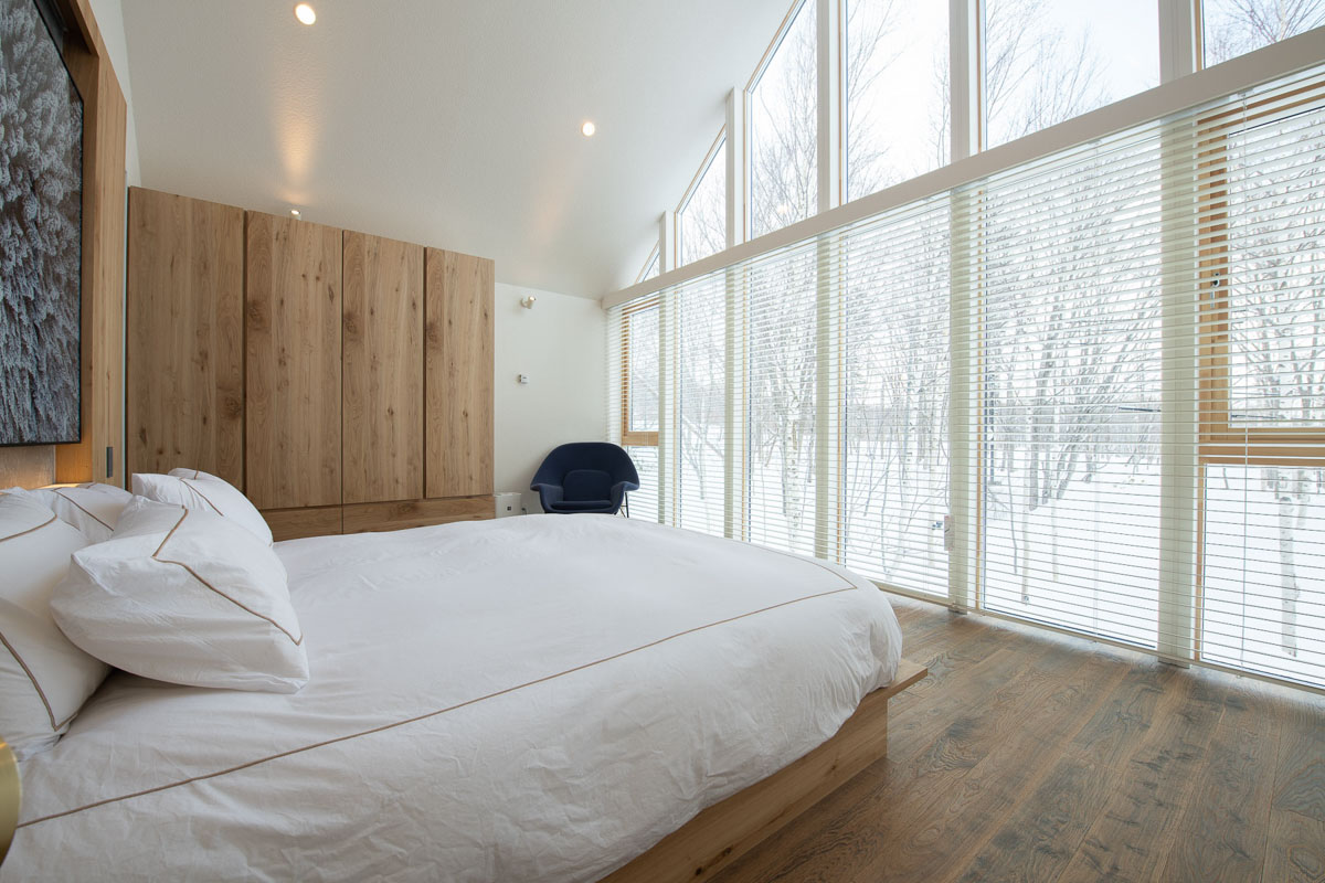 白樺林を望む全面ガラス窓の寝室は森で眠るような心地よさ