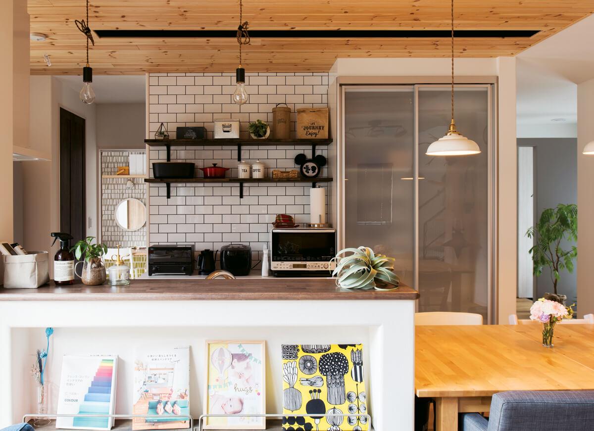 キッチンの白壁の一部はタイルにしてアクセント。生活感がなるべく出ないよう、リビングからの景色にも配慮した