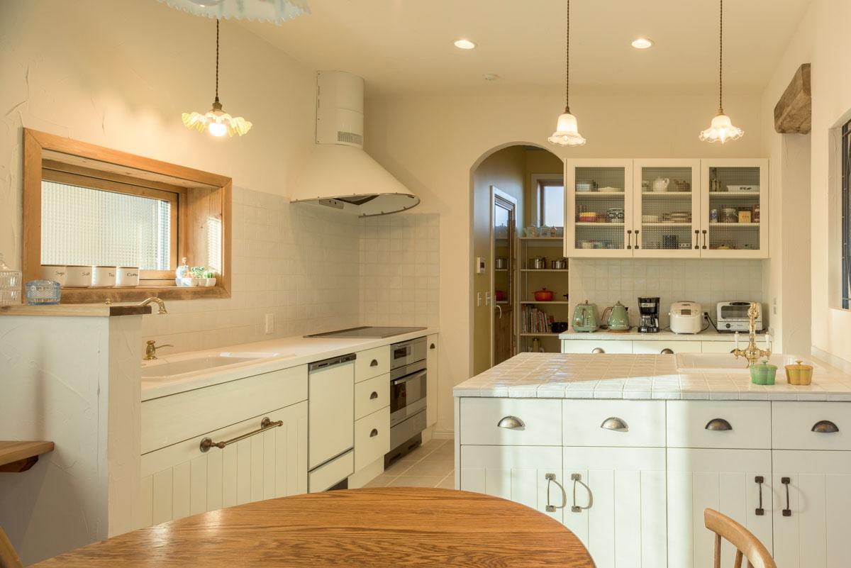 壁付けのI型キッチンに、2つ目のシンクを備え便利に使えるアイランドを組み合わせたキッチン。隣接して、収納量たっぷりのパントリーを設置した