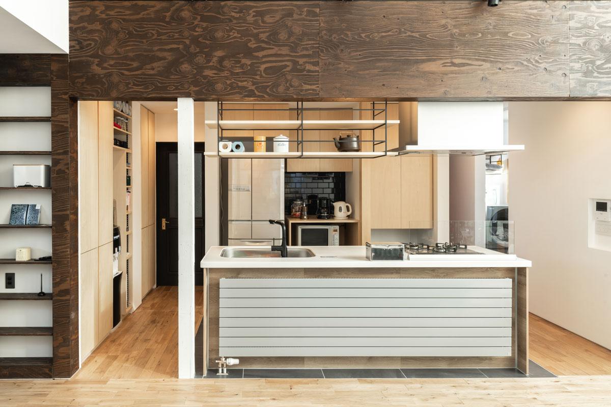 白の人工大理石ワークトップと造作収納など、ナチュラルな色合いでまとめられたキッチンスペース