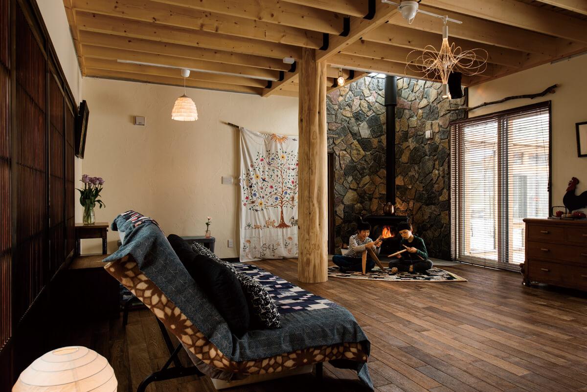 薪ストーブの背後には石をランダムに張り付けて、吹き抜けの2階まで印象的な壁に