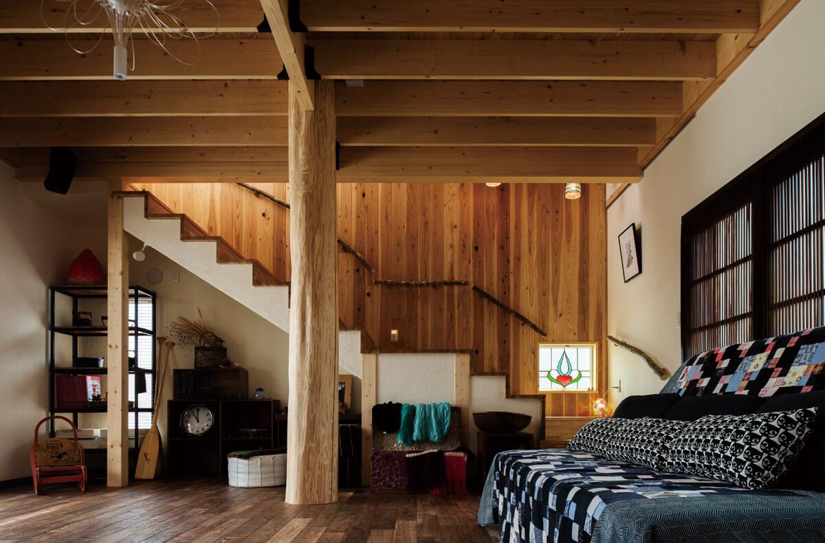 リビングの大空間は2本の太い丸太柱で支える。天井も高めにして開放感あふれる雰囲気。手持ちのステンドグラスを階段のアクセントに。小窓から射し込む光が美しい影を落とす