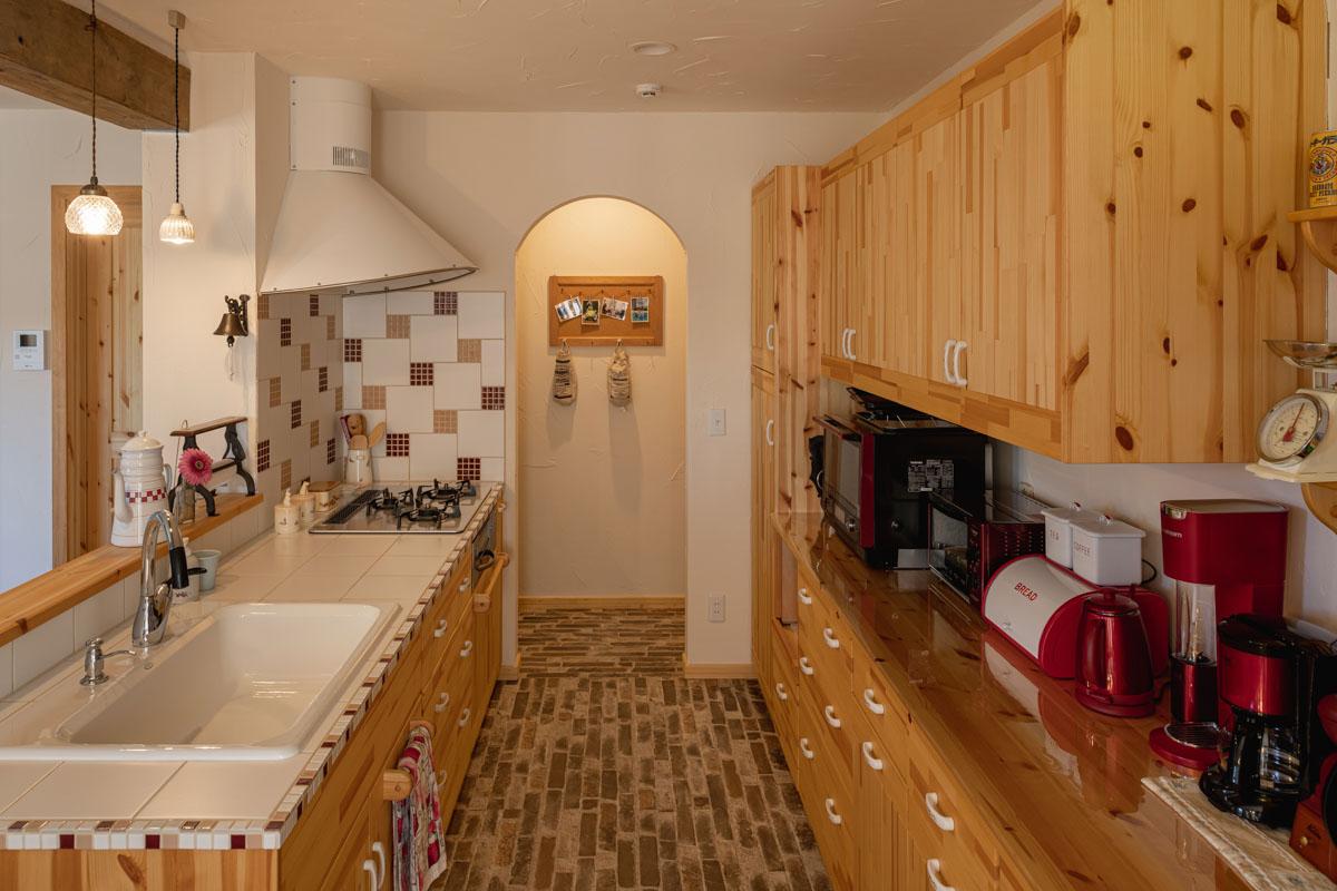 大判と白タイルと縁のモザイクタイル、コンロ壁面のタイル。3種類のタイルが調和するかわいらしいデザイン