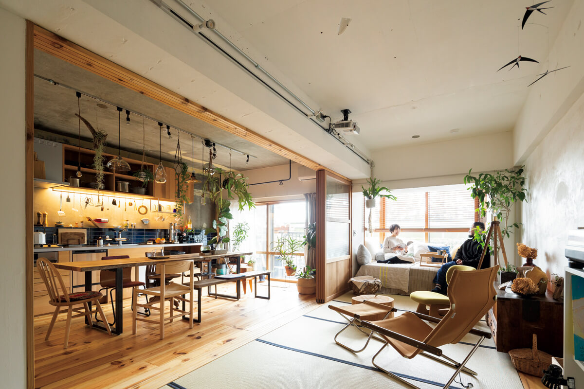間取りを検討し、ゆとりある空間を実現したLDK。和室の壁・天井はご夫妻が自ら漆喰を塗って仕上げ、ダイニングテーブルは空間に合わせて設計し造作した。元はサンルームだった窓辺に空間のサイズに合うベッドを置いてソファ代わりに。庭も見渡せるお気に入りスペースだ