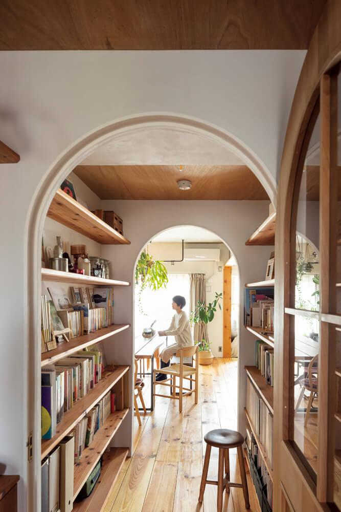 事務所と住居を繋ぐ小さなスペースを、通路を兼ねたライブラリーに。トンネルを思わせるこもり感のある空間がオン・オフの切り換えの役割を果たす