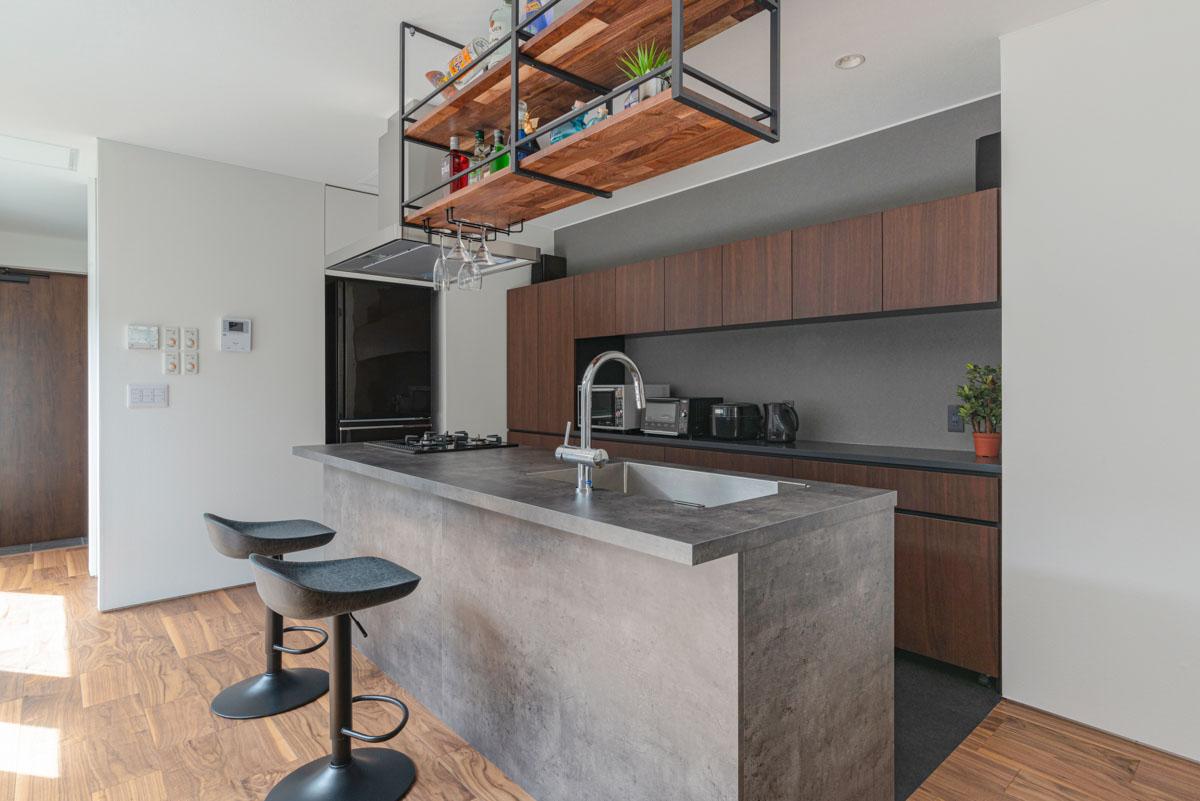 グレーのキッチンに合わせ壁もグレーにし、床は黒にすることで空間が引き締まる。夜はバーの雰囲気でお酒を楽しむスペースになる
