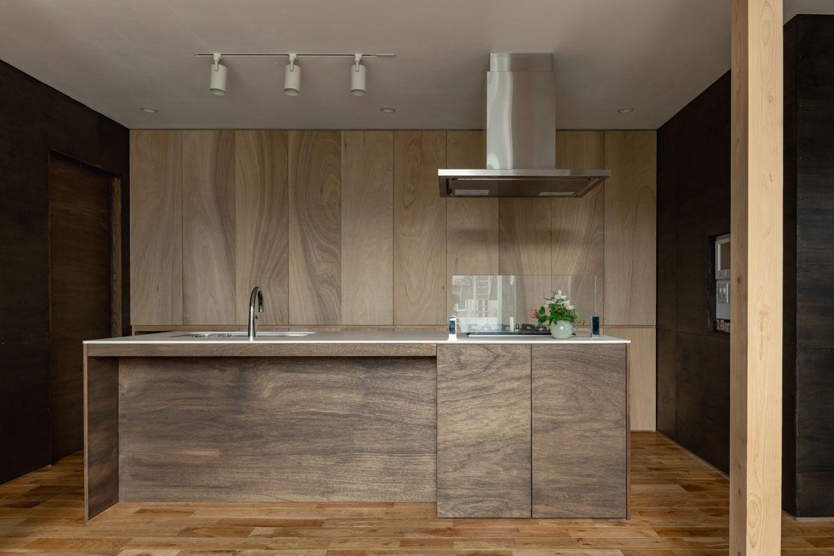 二世帯共用の造作のアイランドキッチンは2人で並んでも作業しやすい広さ。来客が多く、壁面はすべて隠せる収納に