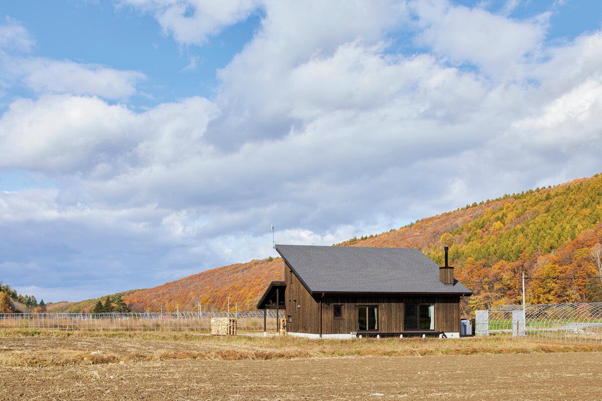 美瑛の田園風景に溶け込むような道南スギ板張りと片流れ屋根のYさん宅。これからリビングとつながるウッドデッキまわりの植栽を整える予定