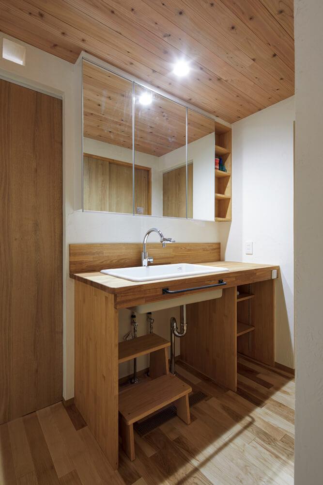 タモを用いて造作した洗面台は、玄関ホールに隣接させ、帰宅後にすぐ手が洗えるようにした。小さな子どもが使いやすいよう踏み台も造作