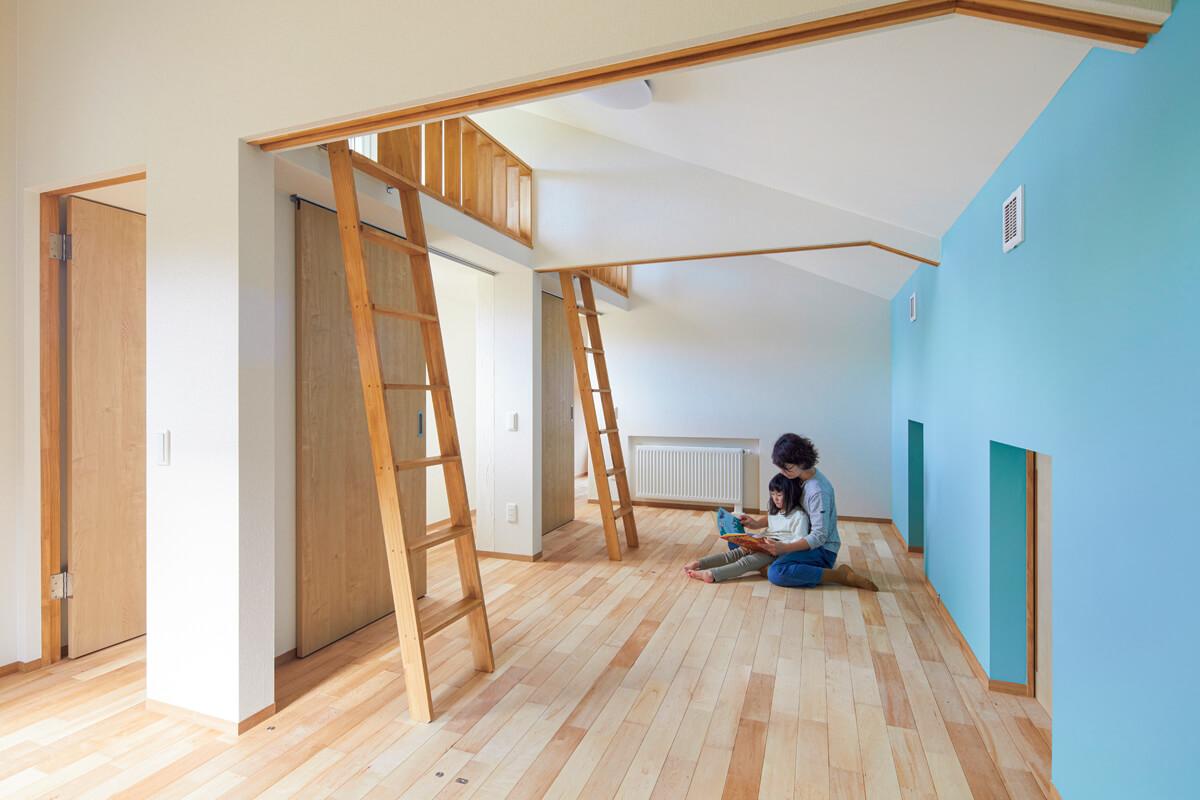 ロフトベッドを備えたオープンな子ども部屋。子どもの成長に合わせて、造作建具で3室に分けられる。水色のアクセントウォールとカエデ無垢床が優しい雰囲気を演出