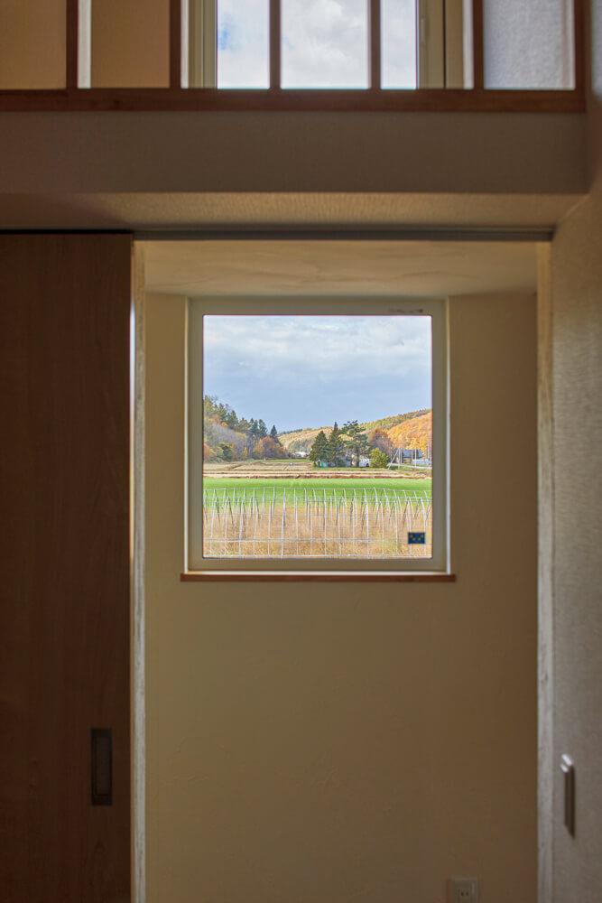2階子ども部屋前の廊下には、周囲の田園風景を切り取る採光窓も設けられている。住まいのあちこちにある窓からの風景も、ご夫妻自慢のインテリア