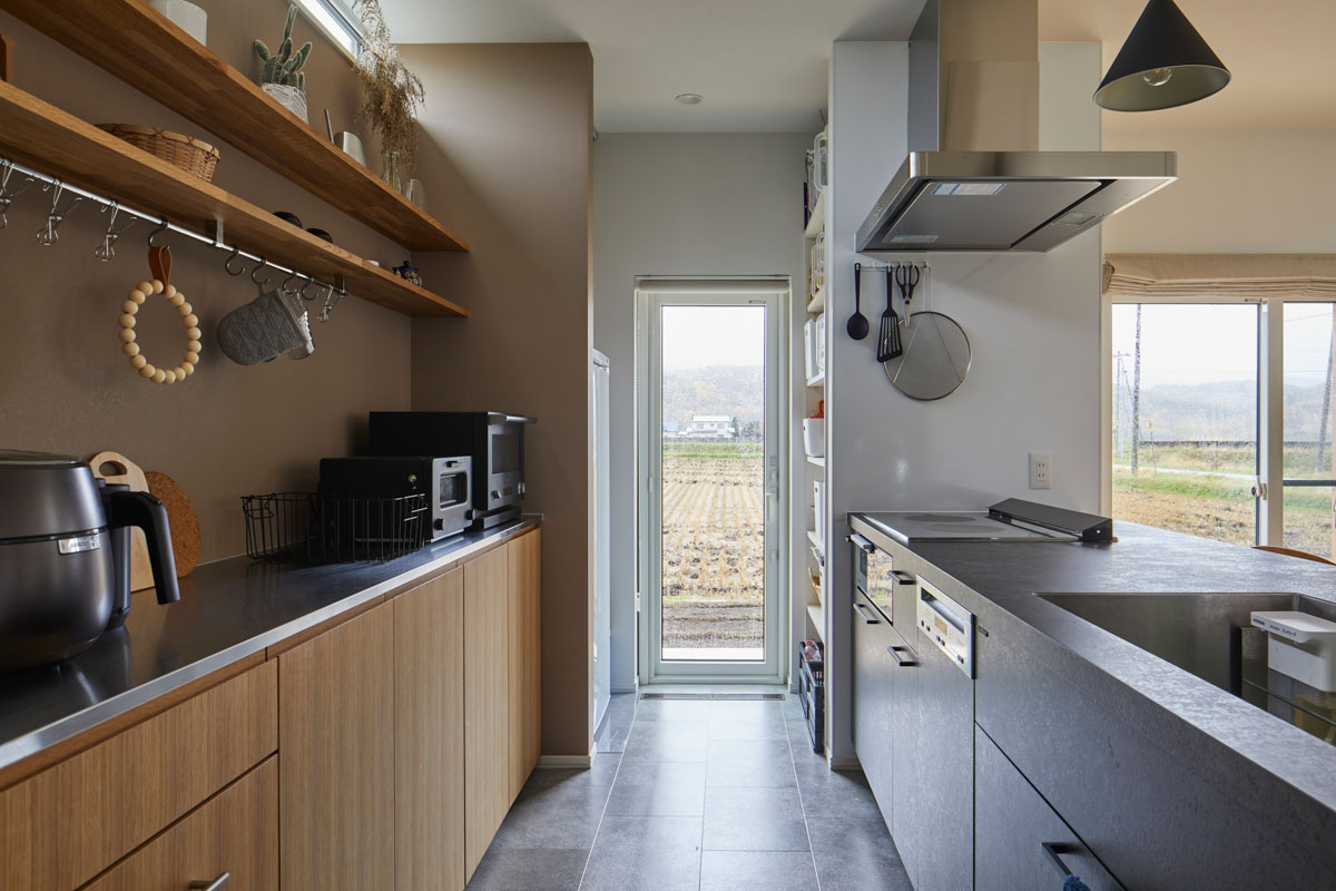 壁面の奥に冷蔵庫と物を収納し見える空間は常にきれいに保てるようにしたキッチン