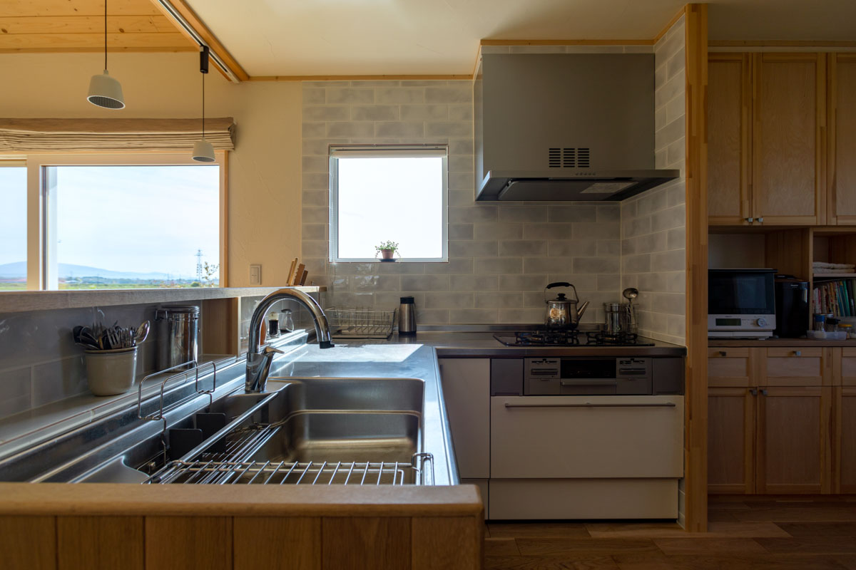 家電や食品の収納などは、奥(写真右)の空間にまとめ、L字型のキッチンはいつでもスッキリ