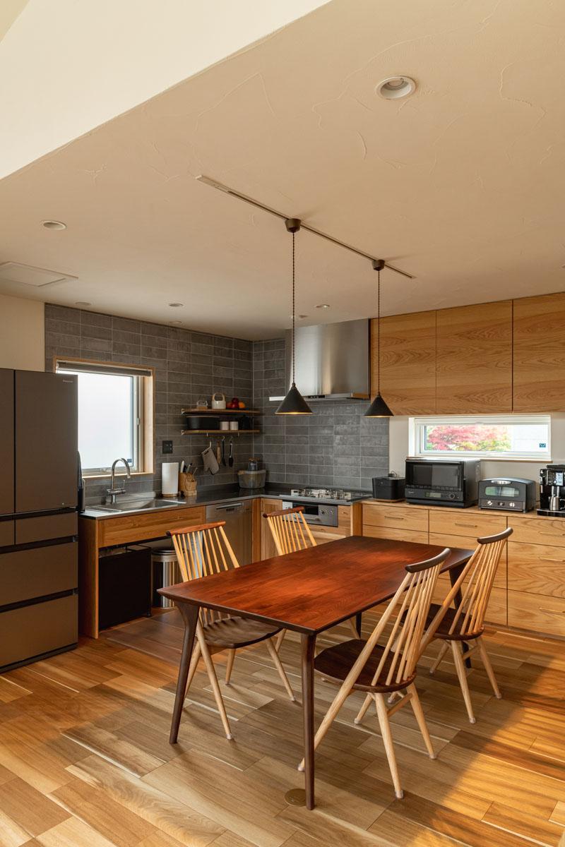 ダイニングを広く使えるよう、キッチンをL型の壁付けに。家電は黒で統一し、造作収納の取っ手は真鍮製を採用