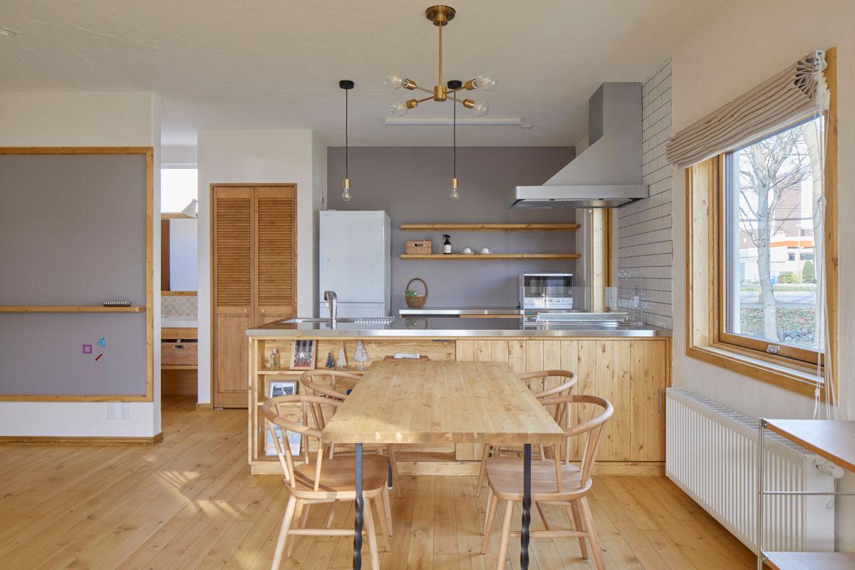 パイン材で造作したキッチンは、腰壁は引き戸仕様の収納になっている。壁面にはタイルを設えた