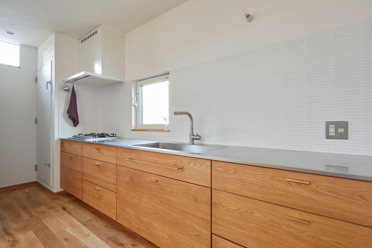 限られたLDK空間にキッチンをコンパクトに収めたいと、壁付け仕様に