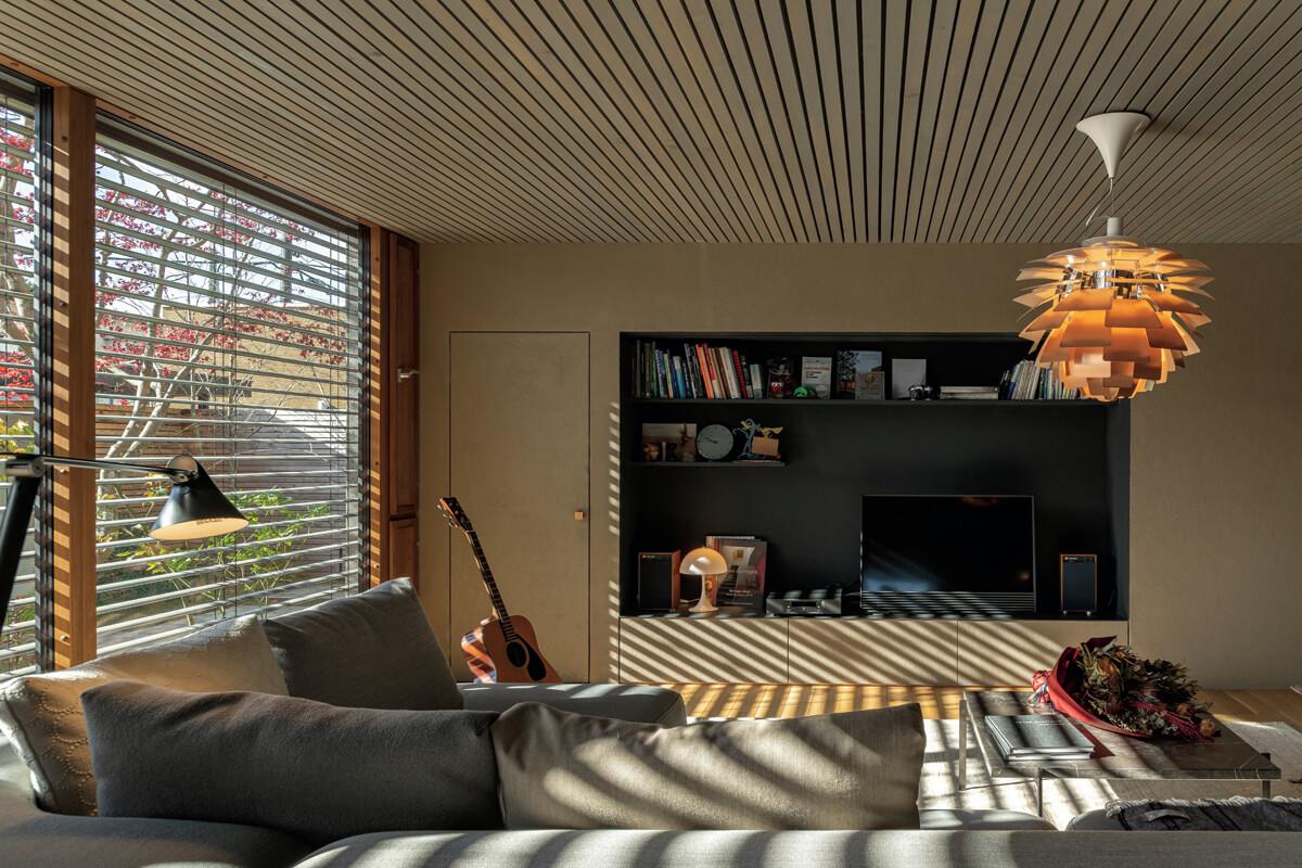きらめく木漏れ日が、外付けブラインドの隙間から射し込むリビング。光と影が織りなす美しいコントラストを家の中に居ながらにして楽しめる。内装には、北海道産ナラ材のフローリング、地元の土をはじめ3種類の土をブレンドした土壁、スギ材で仕上げた天井と、五感で癒やしを得られる自然素材を用いた