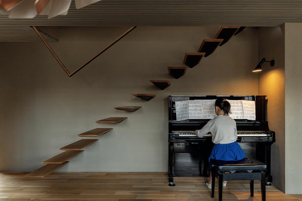 リビングの一角、宙に浮いているかのような意匠性の高い階段の下のスペースをピアノ置き場に。お子さんが奏でる軽快なピアノの音が家に響き渡る