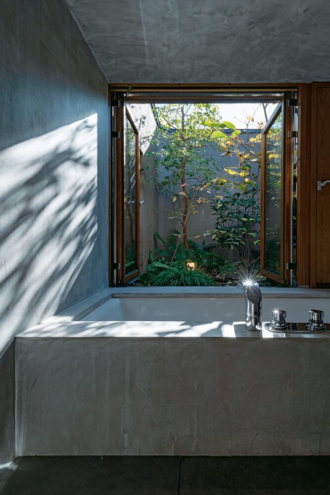 モールテックスで造作した特別感のある浴室の窓からは、植栽で彩られた坪庭の眺めが楽しめる。昨年の夏は坪庭の木にヒヨドリが営巣し、その子育ての様子を観察するのが日々の楽しみになっていたそう。浴室が緑あふれる外部空間とつながることで、心と身体を癒やすバスタイムがさらに充実してリラックスできそうだ