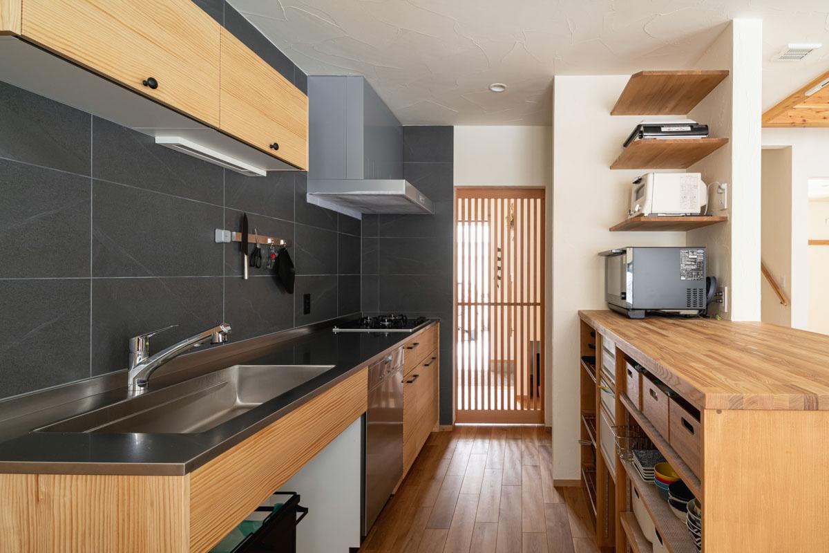 調理に集中できるよう、あえて壁付けにしたキッチン。玄関からそのままキッチンへ入れる利便性の高い配置