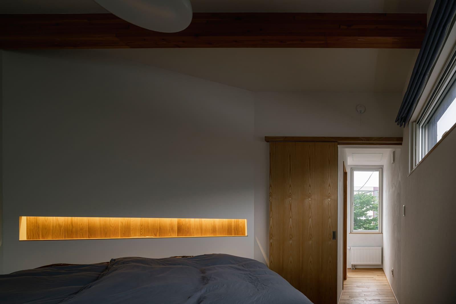 開口を抑え、間接照明を施した寝室は落ち着いた雰囲気。姿見付きのウォークインクローゼットも備える