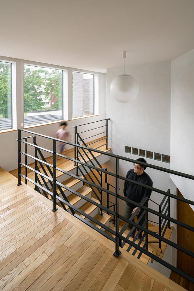 2階の階段ホールに設けられた3連の大開口から入る光と風は、吹き抜け伝いに階下へ