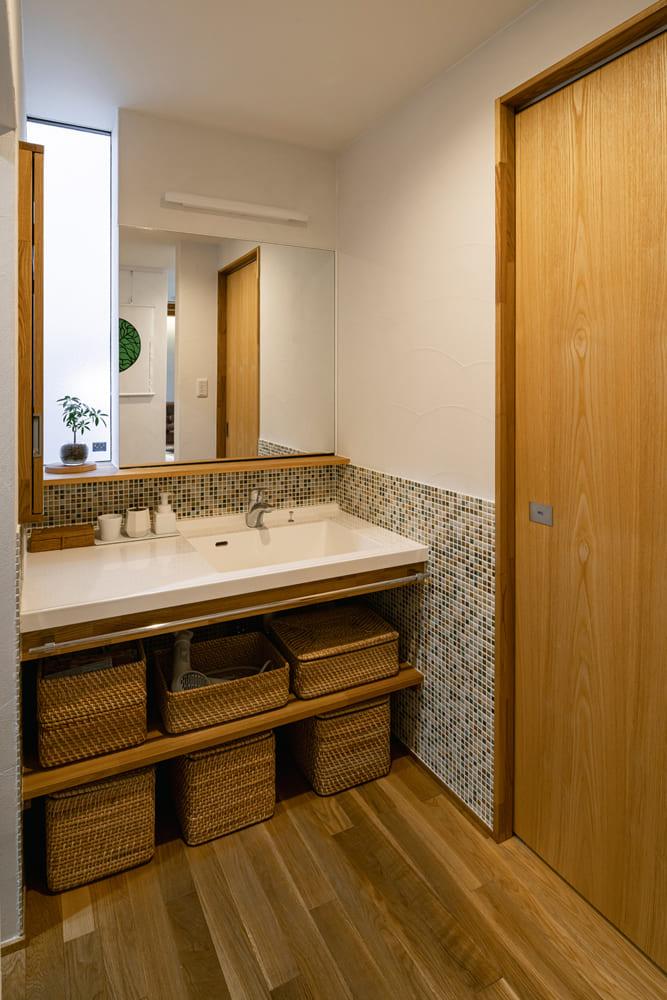 造作仕様の洗面台を設置したゆったりとした洗面室。隣接するトイレの手洗い場も兼ね、ゲストも使いやすい