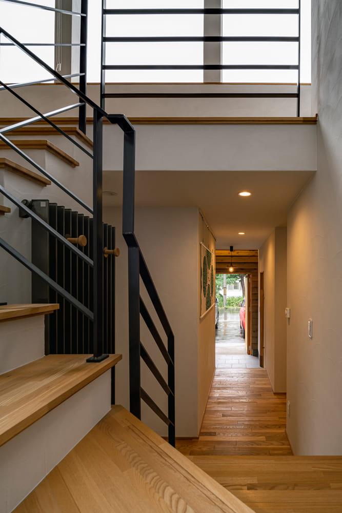 階段から玄関方向を見る。明るさのコントラストが、空間に心地よい広がりを演出