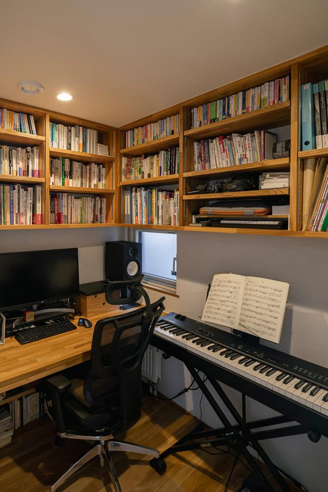 1階の階段横には、Aさん念願の書斎を設えた。造作の書棚やカウンターデスクも備えた2.5帖の空間は、隠れ家のような佇まい