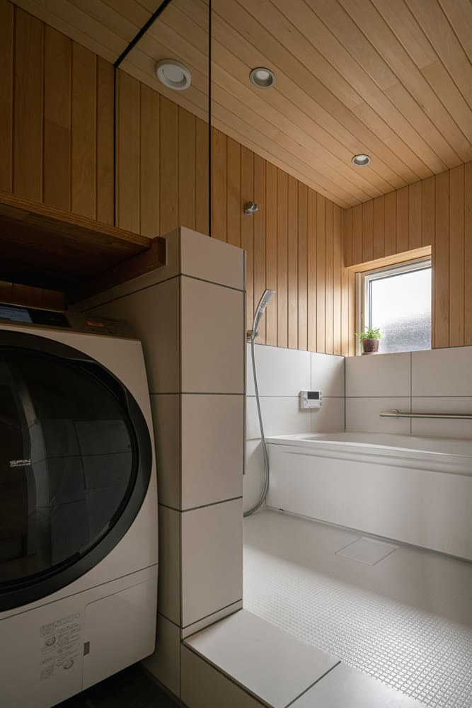 ハーフユニットを採用し、壁と天井に青森ヒバを張った浴室。開放感と風通しを大切にし、あえて建具は用いずオープンなつくりに
