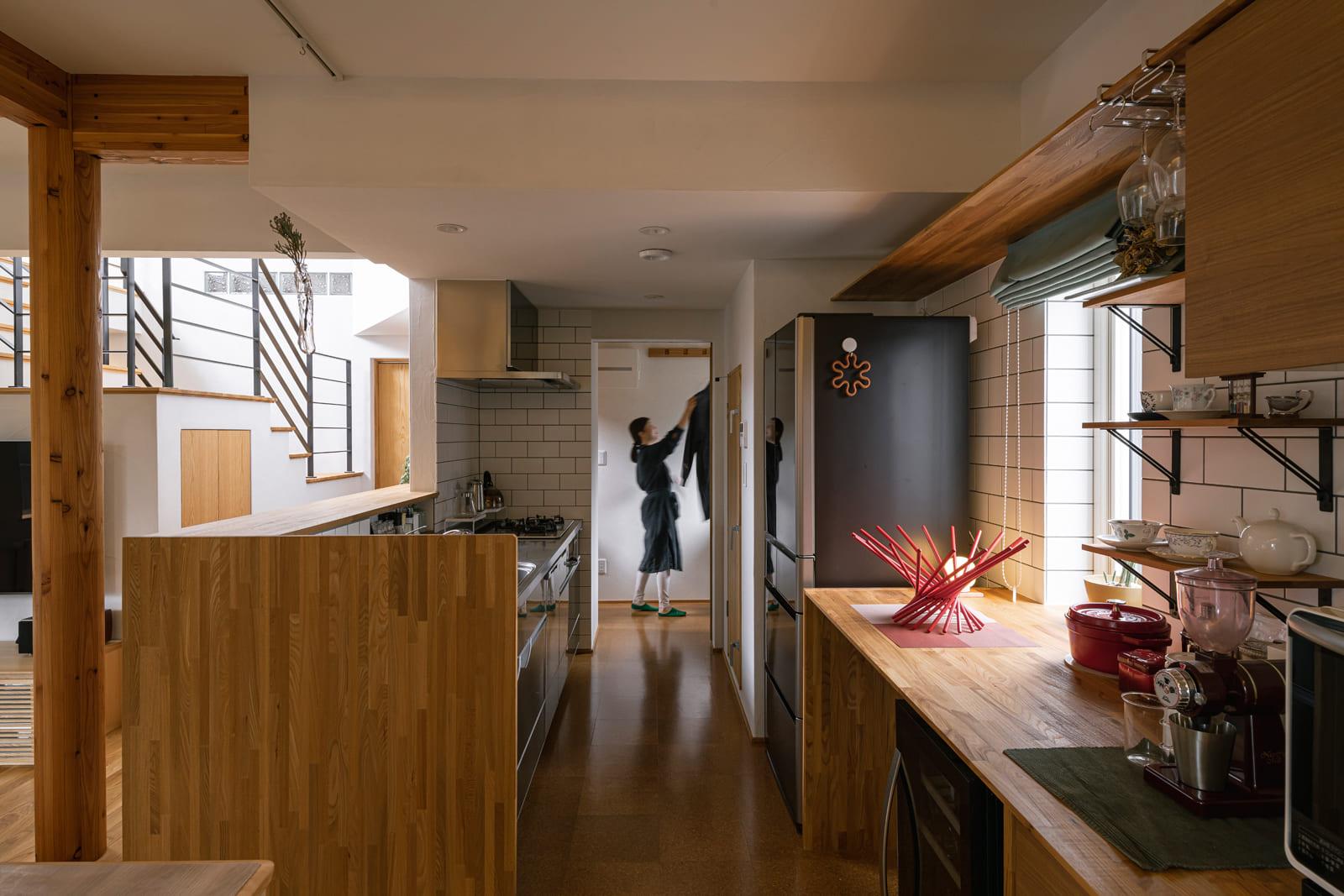 オープンなキッチンは料理好きなご夫妻のこだわりがいっぱい。ステンレスと木を基調に整えたキッチンに隣接して、ランドリーが設えられている