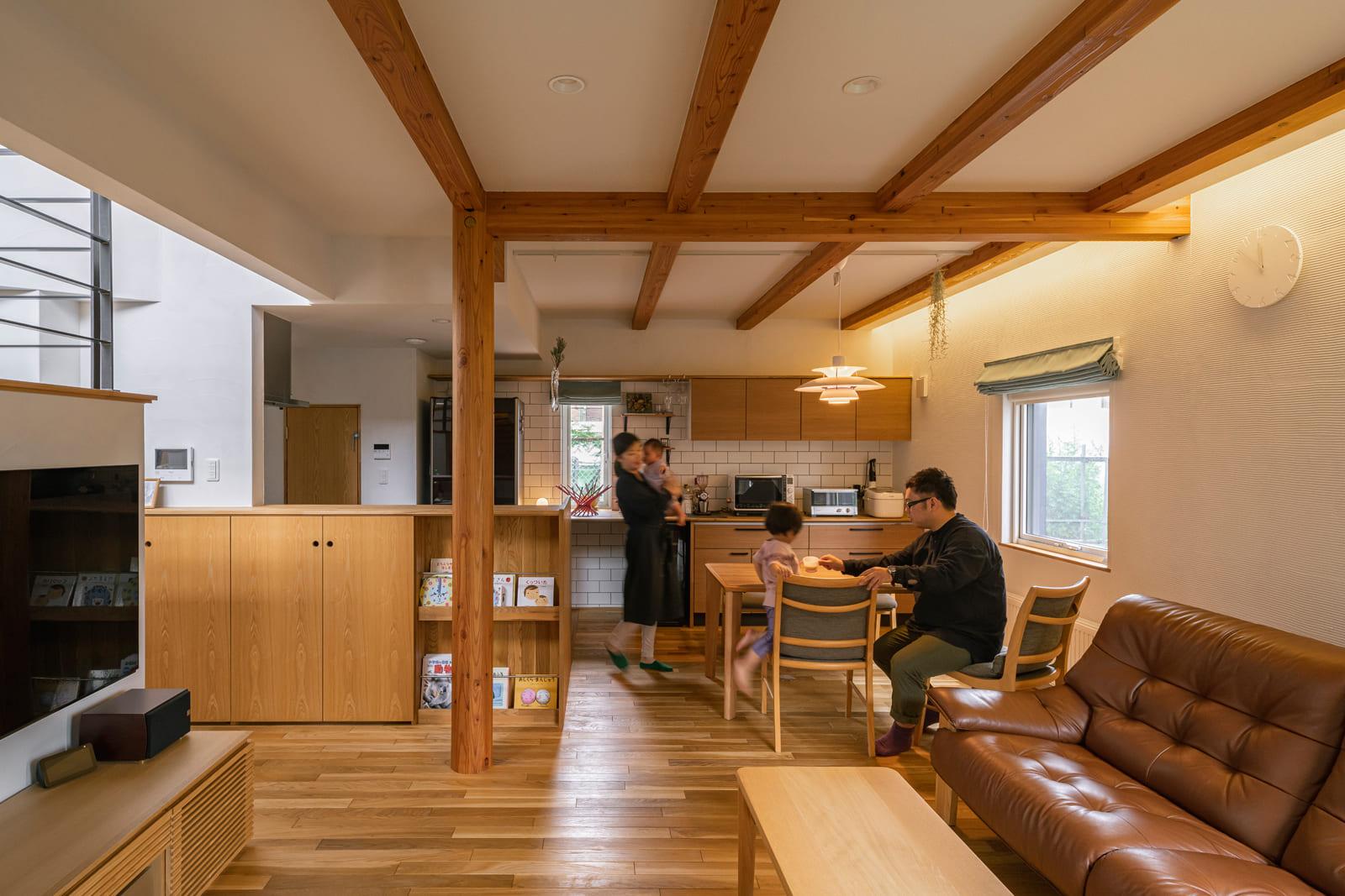 間仕切りなしでつながるLDK。構造を一部現しにした低めの天井がくつろぎ空間に落ち着きと木陰のような心地よさを与える。床はナラ無垢材、壁は珪藻土仕上げ