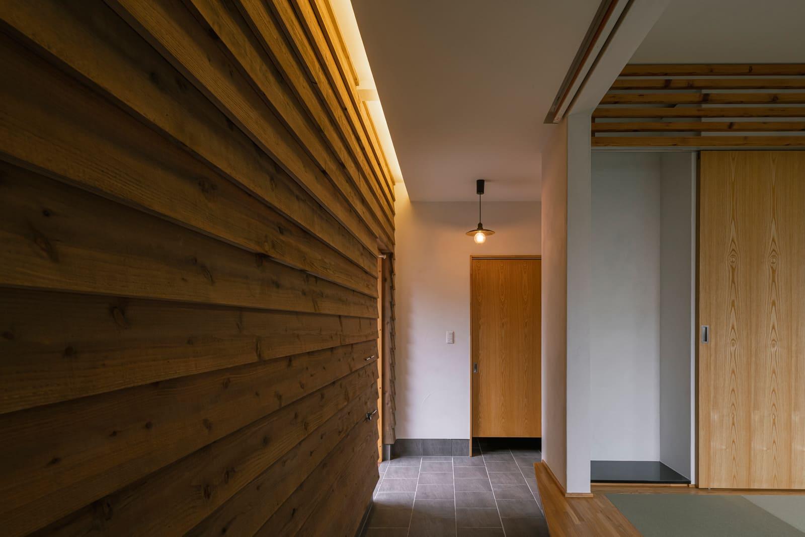 外壁と同じ道産スギを壁に下見板張りにした土間。中と外の中間領域のように見せる設えが空間に奥行き感を演出