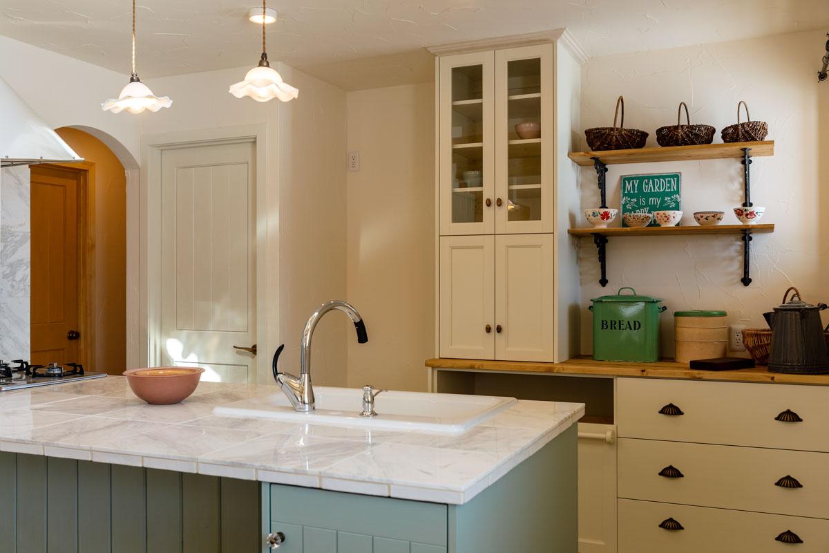 白で揃えたタイルと陶器のシンクの調和が美しい造作キッチン。デザインをはじめ、取手・照明機器など細かい部分までこだわった