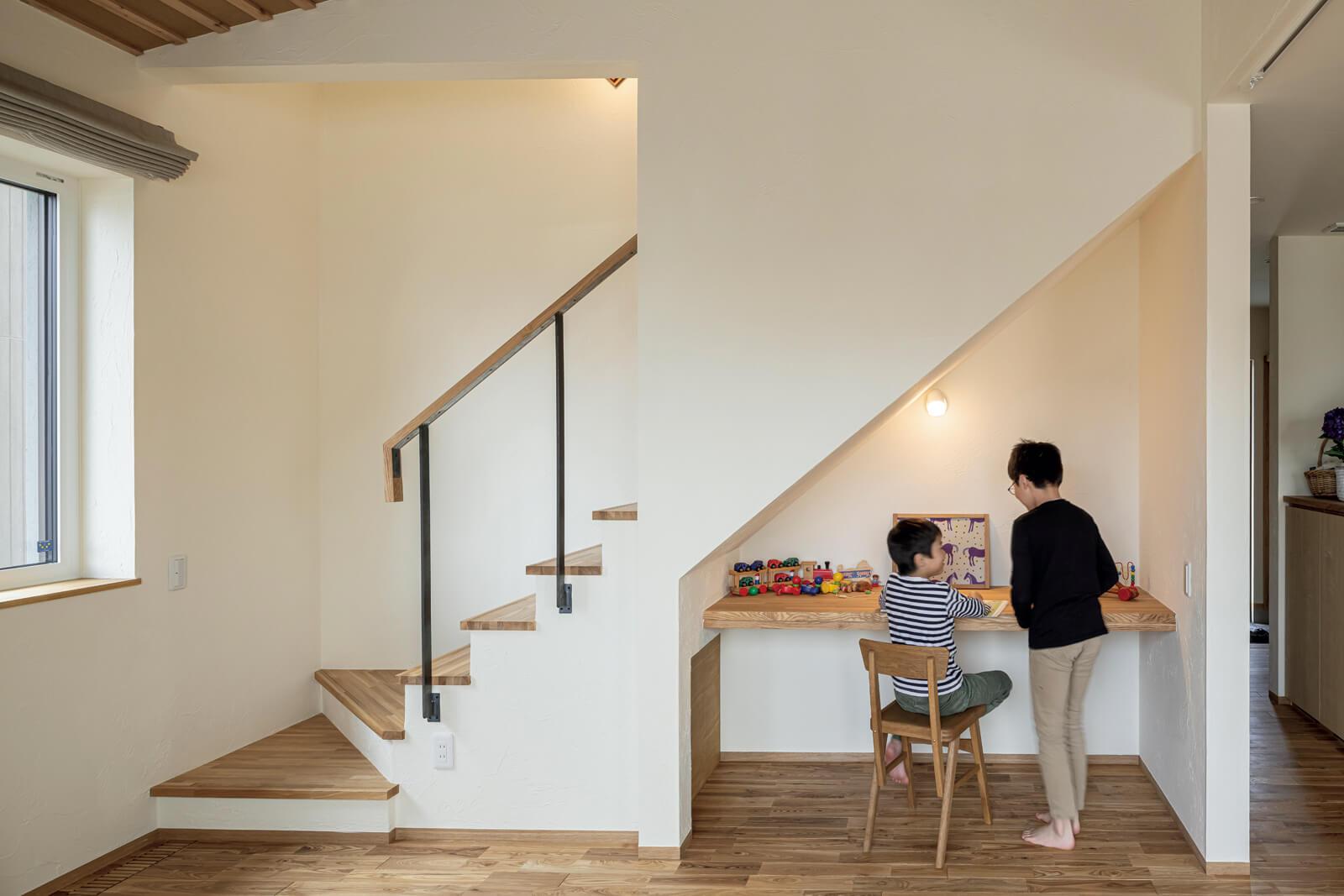 階段下スペースを活用した共用のワークスペース。作業台や勉強机など、家族がそれぞれに利用できる