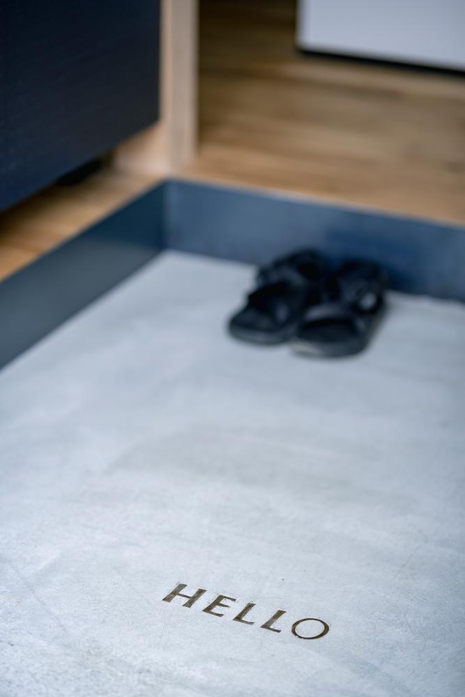 玄関の床に埋め込まれた真鍮レター。訪れた人を「HELLO」の文字がかわいらしく迎えます。「タイルの床にする予定でしたが、このアイデアを実現したくてモルタルに変えてもらいました」とYさん