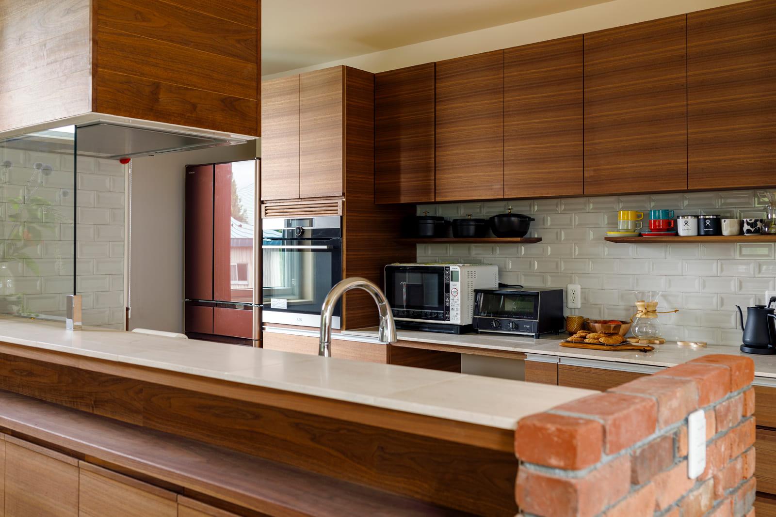 古レンガとウォールナットの組み合わせが、落ち着いた上質な雰囲気を演出するキッチン。「背の高い私に合わせてつくってくれたキッチンなので使い勝手も抜群です」