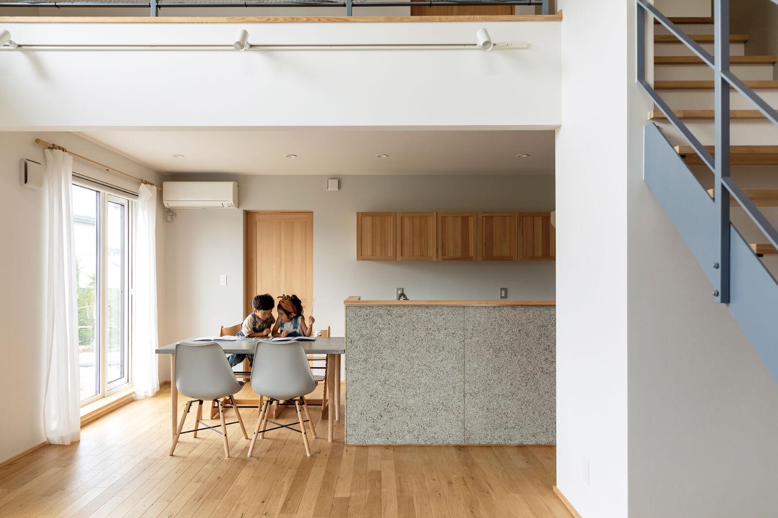 木毛セメント板の腰壁がポイントのキッチン。テーブルをキッチンに横付けしたストレートダイニングで、家事効率をアップさせた。ダイニング後ろの扉の奥は寝室