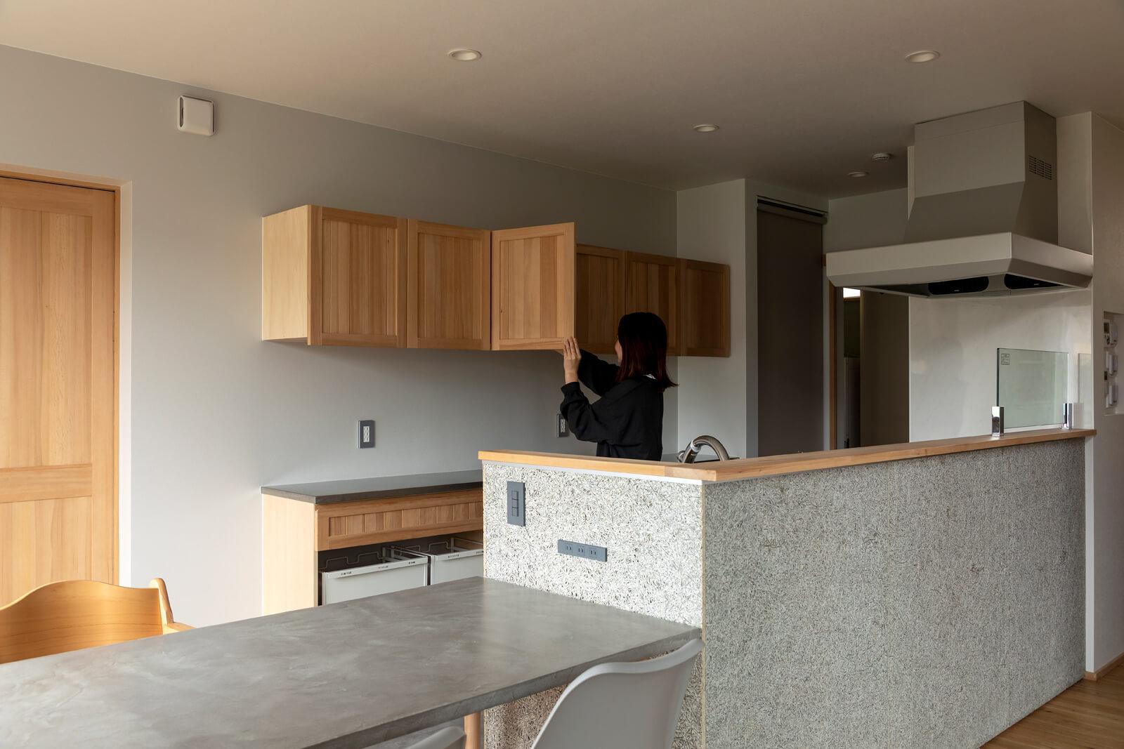 ミーレの大型食洗機や造作収納、グレーの木毛セメント板の腰板。使い勝手と好きなテイストで設えた奥さん自慢のキッチン