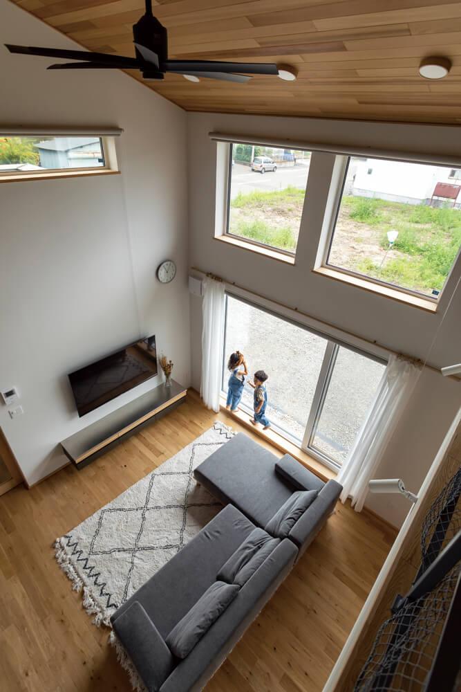 子ども部屋のある2階の階段ホールからリビングを見る。大きな吹き抜けは、家族の気配を家中に伝える装置としても機能する