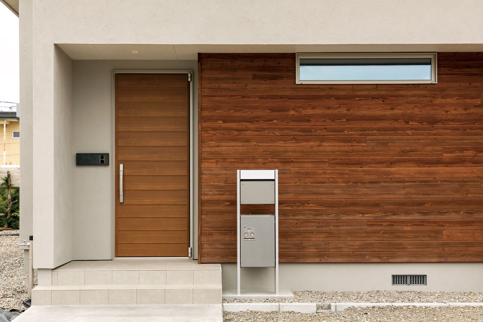 玄関まわりに張ったスギ板が塗り壁の外観にアクセントを与える