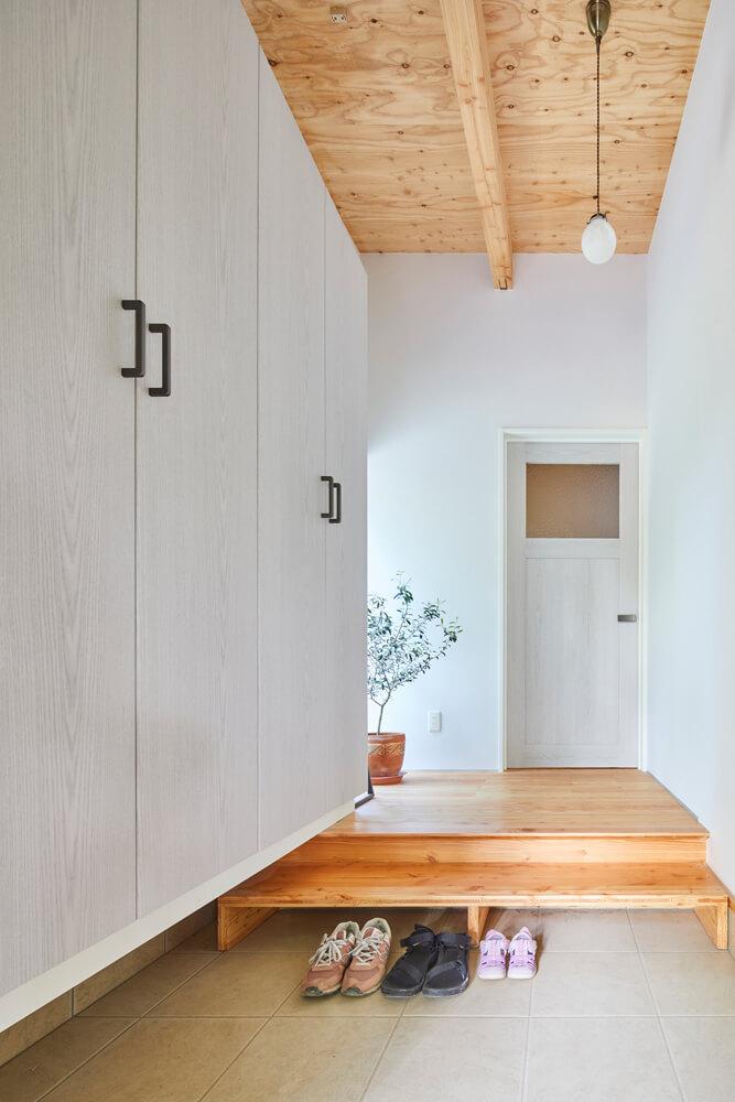 白と木目を基調にした明るい玄関。上がり框の前には、小さな子どもが上り下りしやすいよう、低めの靴脱ぎ台を置い
