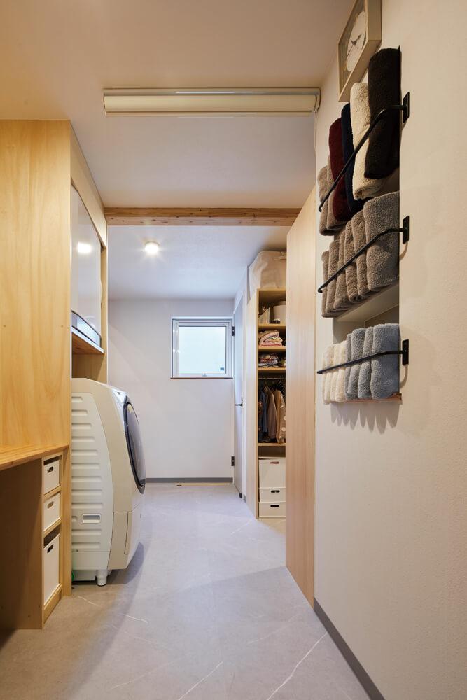 ガス式乾燥機や洗濯機も造作棚にすっきり収まるユーティリティ。乾いた衣類は隣接するウォークインクローゼットにすぐしまえる。アイアンのバーをつけたタオル収納も造作